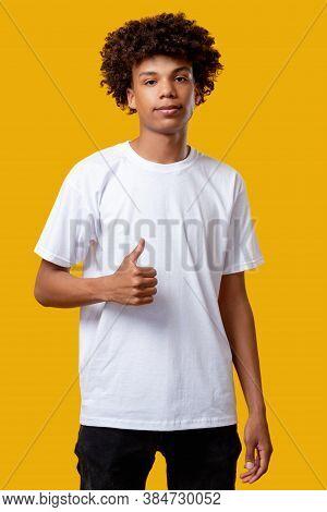 Like Gesture. Social Pressure. Relaxed Black Teenager Boy Feeling Confused Showing Thumb Up. Looking