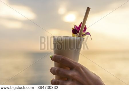Female Hand Holds A Glass With A Pina Colada Cocktail On A Background Of Sunset Sky On A Tropical Be