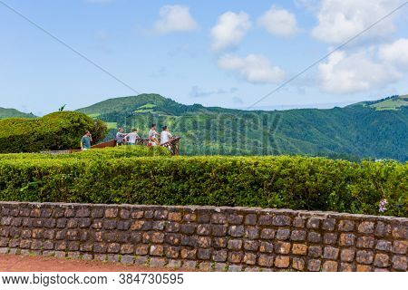 Furnas, Sao Miguel, Azores island, Portugal, August 14, 2020: Tourists watching lagoa das Furnas from Pico do Ferro scenic viewpoint