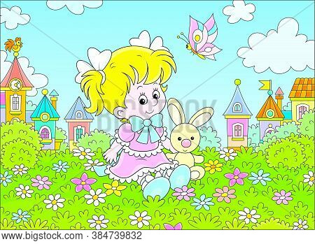 Cute Little Girl In A Beautiful Pink Dress Sitting With A Small Toy Rabbit Among Flowers On A Green