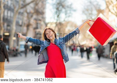 Autumn fashion sale happy woman walking with shopping bags on La Rambla street in Barcelona. Shopper Asian girl ecstatic with open arms holding purchases excited.