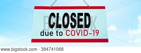 Closed COVID-19 sign hanging on window of shop. Businesses going bankrupt, barber shop, restaurants, hotels, stores, non essential services leading to economic downfall and unemployment.