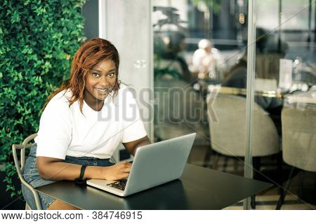 smiling woman in a bar with laptop