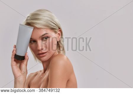 Portrait Of Young Woman With Perfect Fresh Skin Looking Aside, Holding And Advertising Cosmetic Skin
