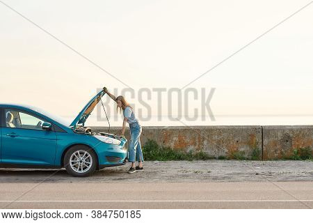 Full Length Shot Of Young Woman Looking Under The Hood Of Her Broken Car, Trying To Repair It On Her