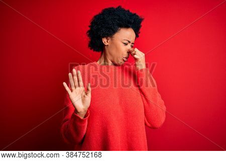 Young beautiful African American afro woman with curly hair wearing casual sweater smelling something stinky and disgusting, intolerable smell, holding breath with fingers on nose. Bad smell