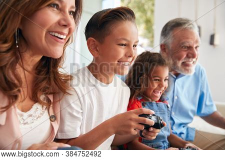 Hispanic Grandparents With Grandchildren Playing Video Game At Home Sitting On Sofa Together