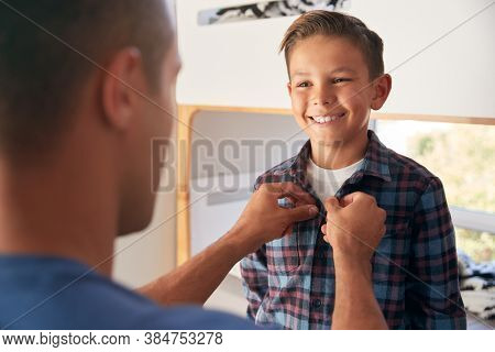 Hispanic Father Helping Son To Get Dressed In Bedroom In Morning
