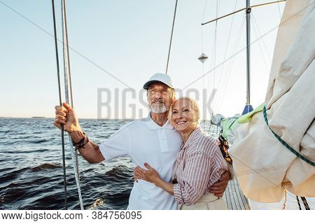 Loving Senior Couple Enjoying Vacation And Looking To The Distance. Mature Couple Standing Together