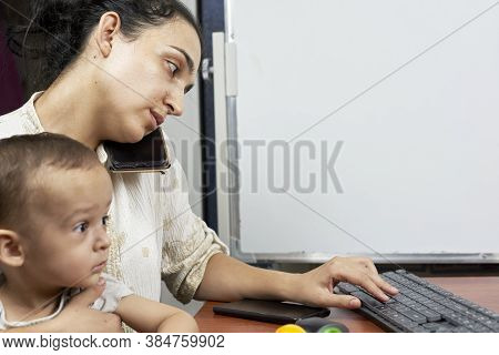 Mommy Talking On The Phone. Young Mother Taking Care Her Baby While Working At Home. Mother And Son