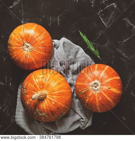 Raw Pumpkins On A Black Stone Background. Top View, Flat Lay. Thanksgiving And Halloween. Photo Tone