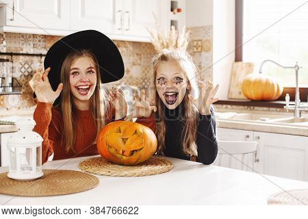 Two Girls At Home In The Kitchen In Costumes And Makeup For Halloween Sit With A Pumpkin, Play Aroun