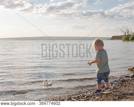 Little Boy Throws Stones In Water. Sunset. Happy Childhood.