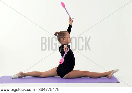 Rhythmic Gymnastics. Girl Gymnast Sitting On A White Background With Gymnastic Maces. Children And S