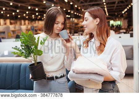 Female Friends Smelling Scented Candle At Furnishings Store