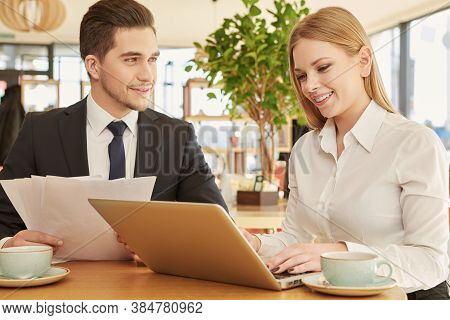 Admiring Partnership. Handsome Businessman Smiling To His Female Colleague As She Is Typing On Her L
