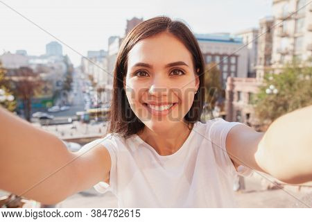 Charming Happy Young Woman Taking Selfies While Sightseeing. Cheerful Woman Smiling Joyfully, Taking