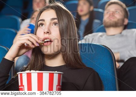 Perfect Movie Snack. Attractive Brunette Female Eating Popcorn While Watching Movies At The Local Mo