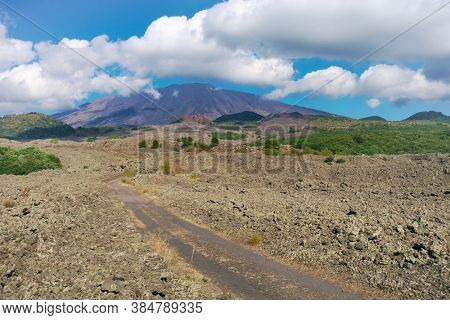 dirt road to Etna Mount crosses volcanic landscape of Sicily landmark of nature