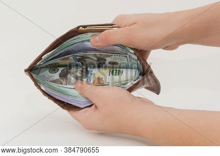 Close-up Of Female Hands Holding An Open Wallet Full Of Money. The Idea Is Wealth, Prosperity, Prosp
