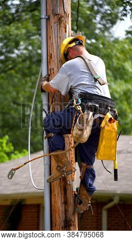 Lineworker Descends Telephone Pole After Repairing Problem With Telephone Lines.  He Has On A Yellow