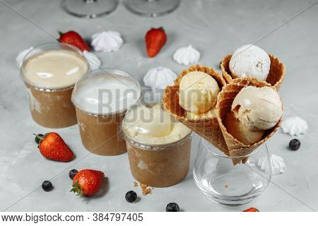 Ice Cream In A Waffle Cone On A Light Background. The Ice Cream Is Melting. Waffle Cones And Strawbe