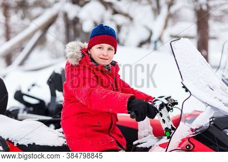 Cute boy in a red parka down jacket outdoors on beautiful winter snowy day on snowmobile