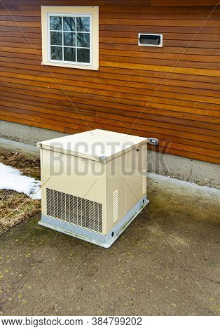 A Residential Standby Generator At The Wall Of A Wooden House