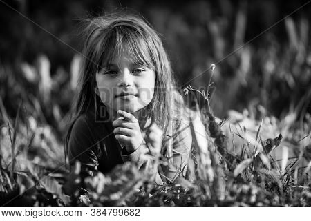 Cute little girl laying in the grass. Black and white photo.