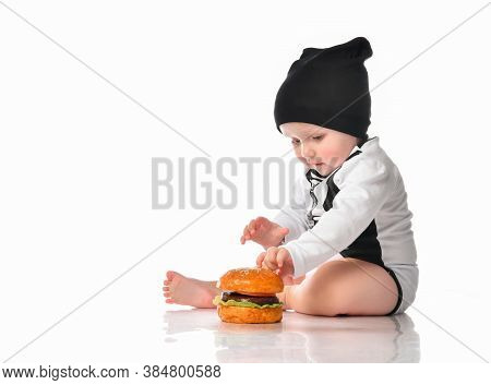 Baby Boy In Casual Outfit Sitting On White Studio Floor Touching Fresh Hamburger. Toddler Child And