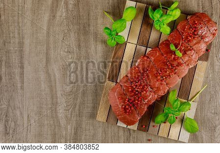Raw Uncooked Beef Tenderloin On Wooden Table With Basil.