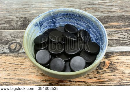Round Black Licorice Candies In Small Ceramic Snack Bowl On Table