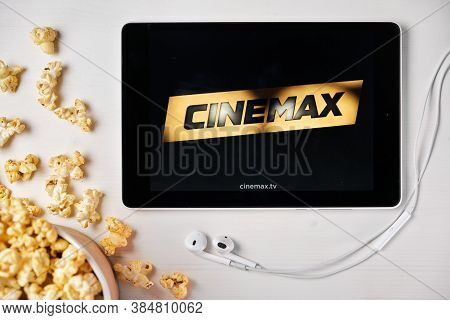 Cinemax Logo On The Tablet Screen Laying On The White Table With Scattered Popcorn And Apple Earphon