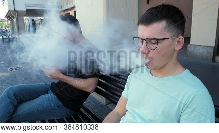 Man In Glasses Smoking Vape And Disturbing Another Man With A Smoke.