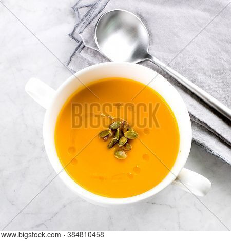 Pumpkin Soup In White Bowl On Marble Table. Autumn Seasonal Soup Dish. Top View, Copy Space.