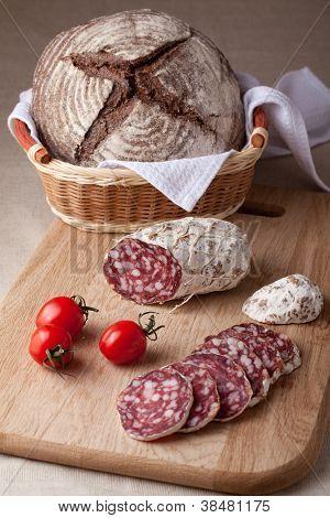 Slices Salami On Board, Cherry Tomatoes Bread In Breadbasket