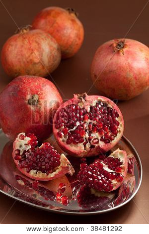 Pomegranate Slices And Seeds On Silver Tray