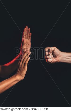 Black Lives Matter. Races Fights. White Male Fist Threatening African Opened Hands Isolated On Dark.