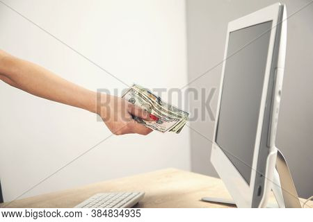 Close-up Of Hands Shopping Paying Online Using Laptop While Holding Us Dollars.