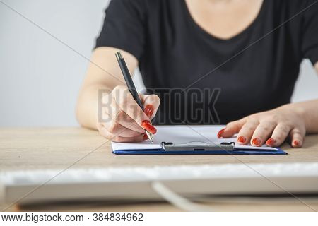 A Woman Writes With A Pen In A Notebook.