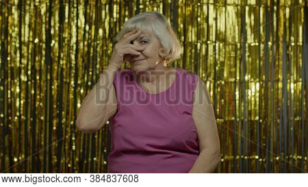 Portrait Of Nosy Curious Senior Old Lady With Blond Hair Closing Eyes With Hand And Spying Through F