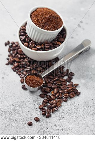 Fresh Raw Organic Coffee Beans In White Bowl And Powder On Ligh Table Background And Round Steel Sco