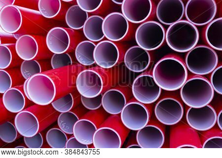 Red Plastic Pipes For Building Stacked On Top Of Each Other. The Colors And Patterns Of Pvc Pipes Fo