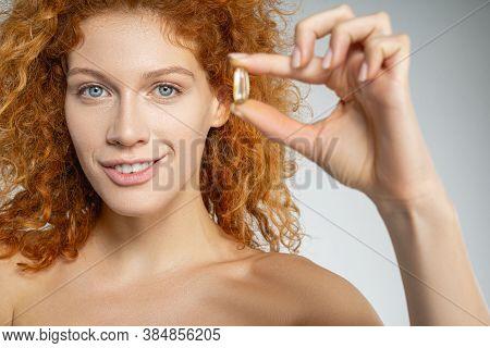 Happy Curly Female Using Medical Vitamins In Capsule