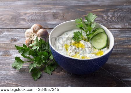 Traditional Greek Yogurt Tzatziki Sauce With Cucumbers And Herbs On Wooden Background