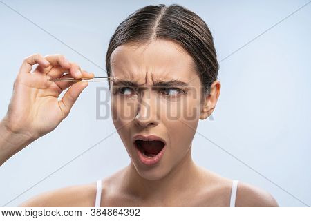 Irritated Young Woman Performing A Beauty Procedure