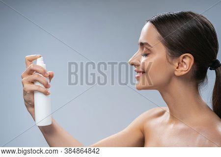 Woman Spraying Thermal Water On Her Skin