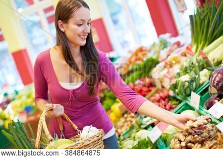 Young smiling woman buys vegetables in health food store