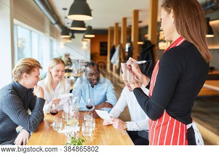 Waitress with notepad in the restaurant waits for the order of the guests