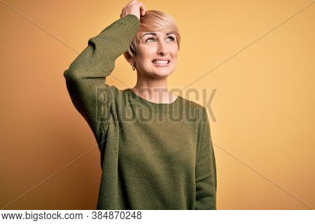 Young blonde woman with modern short hair wearing casual sweater over yellow background smiling confident touching hair with hand up gesture, posing attractive and fashionable